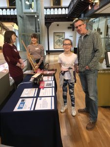 Colour photograph showing some o the team with visitors at our 'Flaky Paint' stall at the Glasgow Science Festival in 2019